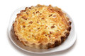 Leek and cheese quiche goats whole on a white plate Stock Photos