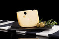 Leerdammer hard cheese on plate on cloth on black background with green olives luxurious cheese still life minimal sparse style Royalty Free Stock Photos
