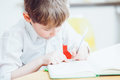 Left handed school boy writing or drawing in book Royalty Free Stock Photo
