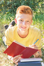Left-handed teen lying and writing on the grass. Royalty Free Stock Photo