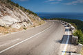 Left turn of mountain highway with blue sky and sea Stock Images