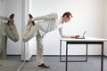 Leg exercise durrng office work standing man reading at tablet in his Royalty Free Stock Photo