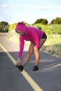 Leg muscle stretch woman in pink hooded top bends to hold her toe and her muscles after exercising Royalty Free Stock Photo