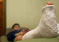 Leg in plaster little boy with broken cast lying on sofa at home and using smart phone focus foreground Stock Images