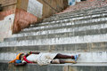 Legged sadhu sleeping on the stairs of a ghat india varanasi may unidentified poverty is increasing in with large Stock Photo