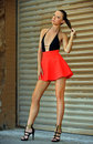 Leggy fashion model wearing black swimsuit and red skirt posing outdoor with metal gate on the background Stock Photography