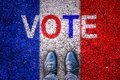 Legs on asphalt with french flag and the word `vote` Royalty Free Stock Photo