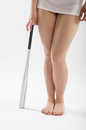 Legs and bat a womans a aluminum baseball resting on the floor Royalty Free Stock Image