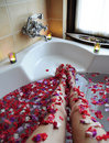 Legs in bathtub with flowers Stock Photos