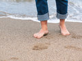 Legs on beach detail of male feet at the with a wave of foaming water Royalty Free Stock Photos