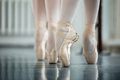 Legs dancers on white pointe near the choreographic training machine young ballerinas Stock Image