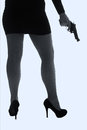 Legs of dangerous woman with handgun and black shoes silhouette stockings artistic conversion Royalty Free Stock Images