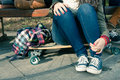 Legs of a girl sitting on a skateboard with his teenage friends in park Royalty Free Stock Photos