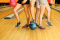 Legs of man and girls with balls in bowling club Royalty Free Stock Image