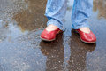 Legs in red shoes in autumn rainy puddle Royalty Free Stock Photography