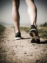 Legs and shoes of a runner photo the young woman jogging on gravel path down country path heavily filtered for atmosphere Stock Image
