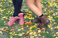 Legs and shoes of young girls standing on the dry leaves and gra grass beautiful autumn day Stock Photography