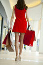 Legs of shopaholic wearing red dress while carrying several pape paperbags Royalty Free Stock Photography