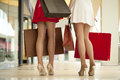 Legs of shopaholic wearing red dress while carrying several pape paperbags Stock Photos