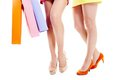 Legs of shoppers female over white background with paperbags in hands Royalty Free Stock Images