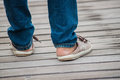 Legs with sneakers back side of standing human wearing jean step on Royalty Free Stock Photography