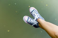 Legs in a sneakers over the water Royalty Free Stock Photo