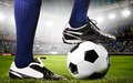 Legs of a soccer player or football on ball on stadium Stock Images