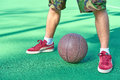 Legs stands near basketball ball Royalty Free Stock Photo