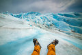 Legs of a tourist in boots against a blue glacier. Shevelev.
