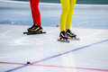 Legs of two girls speed skaters at starting line during competition in skating Stock Images