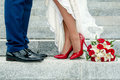 Legs of wedding couple and bouquet Royalty Free Stock Photo