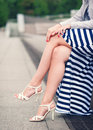 Legs of woman with high heels dressed long striped dress outdoor Stock Photo