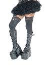 Legs of woman in long black boots.