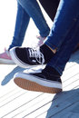 Legs of young girl in jeans and sneakers closeup Royalty Free Stock Photo