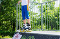Legs of a young roller skater on a cement ramp wearing rollerblades balanced at the skate park ready to launch off for speed and Royalty Free Stock Photos