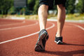 Legs of young sportsman running on stadium track Royalty Free Stock Photo