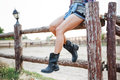 Legs of young woman cowgirl in shorts sitting on fence Royalty Free Stock Photo
