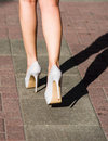 Legs of a young woman in high heeled shoes going along the street on a sunny summer day extreme high heeling this must be Royalty Free Stock Photos