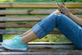 Legs of a young woman in jeans on a bench in the park Royalty Free Stock Photo