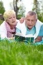 Leisure in the country happy mature couple lying on grass and reading a book countryside Royalty Free Stock Photo