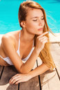 Leisure day by the pool beautiful young woman in white bikini lying poolside and keeping eyes closed Royalty Free Stock Image