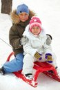 Leisure happy siblings in winterwear tobogganing in park Royalty Free Stock Photography