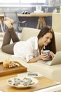 Leisure time at home young woman drinking tea using laptop lying on sofa Royalty Free Stock Image