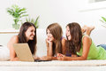 Leisure time three beautiful teenage girls lying on the carpet and surfing internet on laptop Stock Photo