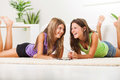 Leisure time two beautiful teenage girls lying on the carpet and listening music from tablet pc Stock Image