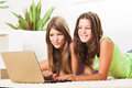 Leisure time two beautiful teenage girls lying on the carpet and surfing internet on laptop Stock Photos