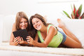 Leisure time two beautiful teenage girls lying on the carpet and surfing internet on tablet pc Stock Image