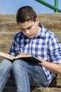 Leisure young pojke som läser en bok i träna med grunt djup Royaltyfri Bild