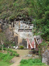Lemo burial site in tana toraja on sulawesi rock wall with tau tau and small tongkonans to carry a coffin to the at ulawesi Royalty Free Stock Images