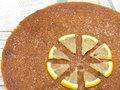 Lemon and almond cake freshly baked with out of focus recipe as background Stock Images